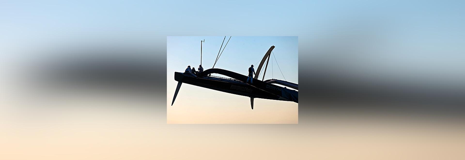 Le homme de barre sur les 90 ? (27.4 m) Amérique ? le gagnant BMW Oracle de tasse de s est rapetissé par le daggerboard incurvé dans l'ama au vent.